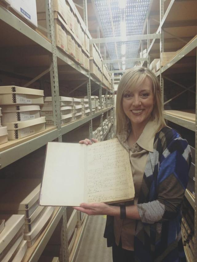 County Council member Aimee Winder Newton holding the minutes from the first County meeting in March 1852.