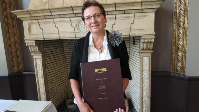 Terry B. Nelson holding her CIMA Lifetime Achievement Award.